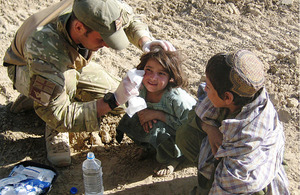 Lance Corporal Craig Murfitt gives first aid to an Afghan girl