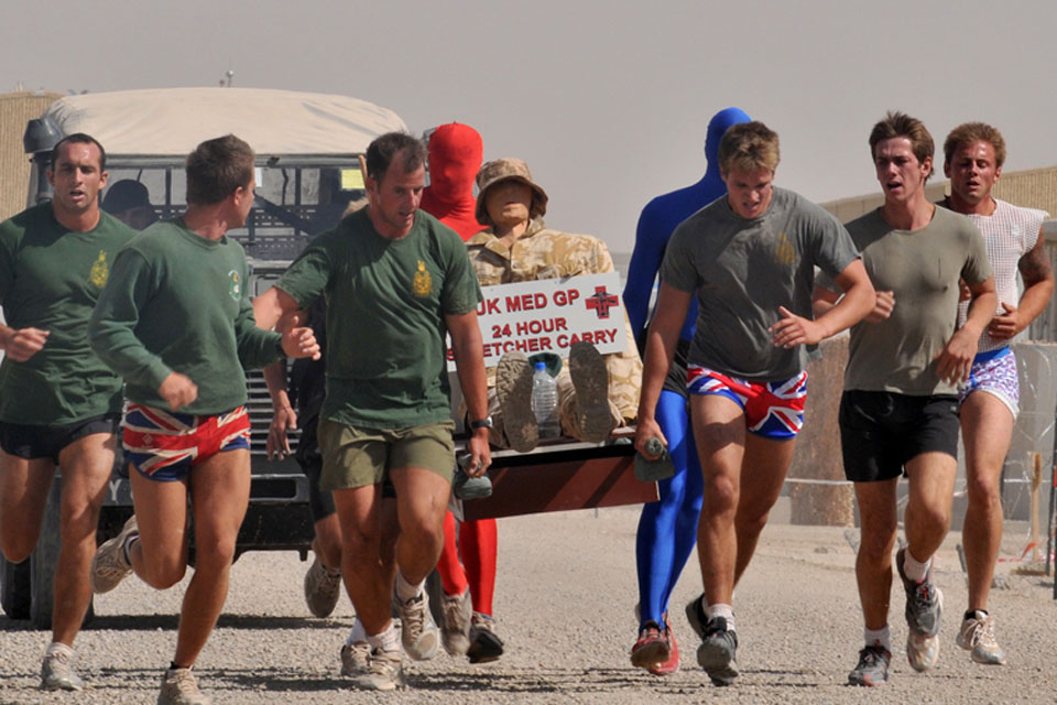 Royal Marines wearing fancy dress taking part in the stretcher-carry around Camp Bastion