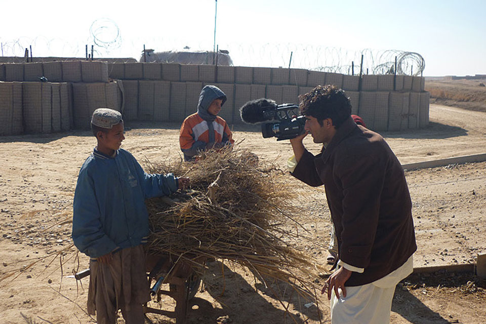 An Afghan cameraman films two local boys outside an ISAF patrol base
