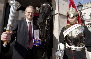 Former Guards Officer and Olympic Pentathlete, Dominic Mahony, displays the Bronze medal he won at Seoul in 1988, and an authentic Olympic torch outside Horse Guards, where an Olympic exhibition has opened