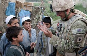 A British soldier chatting to Afghan children during a joint patrol with the Afghan National Police and Afghan National Civil Order Police in the Bolan area