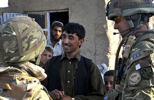 A British soldier talks to a local shop owner via an interpreter (left) (stock image)
