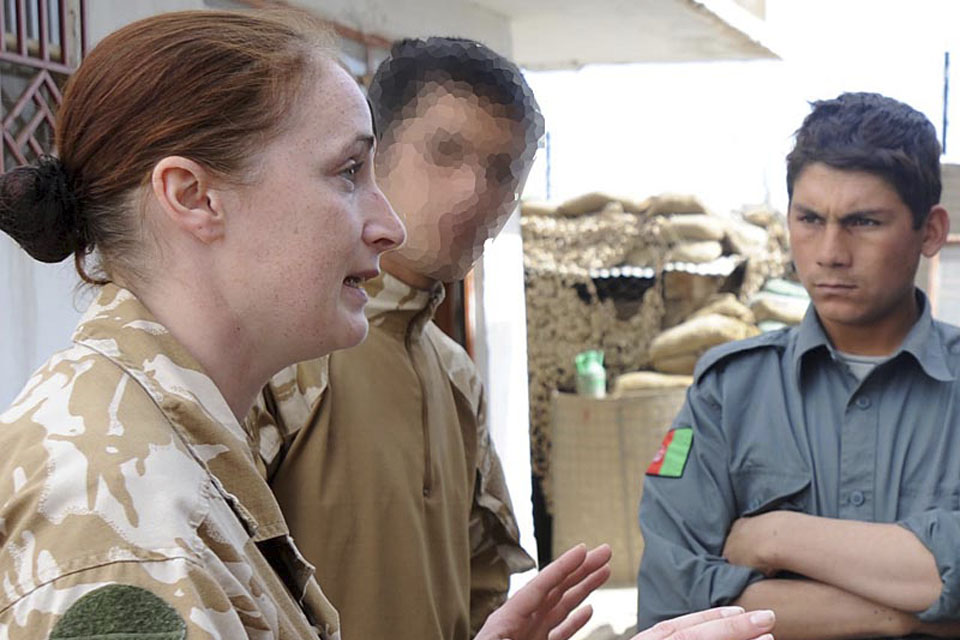 Corporal Natasha Richards, Royal Military Police, uses a local interpreter, whose features have been disguised for security reasons, to instruct up-and-coming members of the Afghan National Police in Musa Qal'ah (stock image)