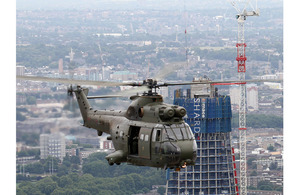 A Royal Air Force Puma HC1 helicopter from 230 Squadron, based at RAF Benson in Oxfordshire, is pictured flying past the construction site of 'The Shard' skyscraper during a training flight over London