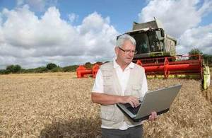 a farmer using a laptop on front of a combine harvester