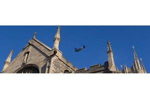 A vintage DC-3 Dakota aircraft flies over St Edmundsbury Cathedral