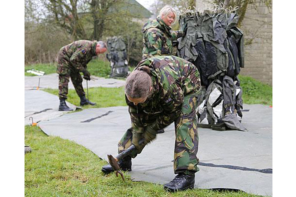 RAF reservists lay a groundsheet for a tented structure