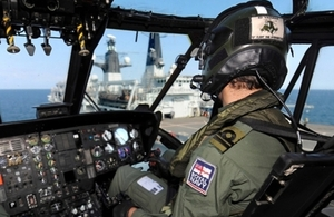 A helicopter pilot edges his aircraft closer to HMS Bulwark for landing during Operational Sea Training (OST).