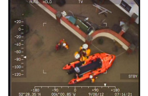 The crew of RAF Valley Sea King Search and Rescue helicopter Rescue 122 assisting members of the Borth lifeboat team who had become caught in debris while searching for trapped persons following severe flooding in western Wales