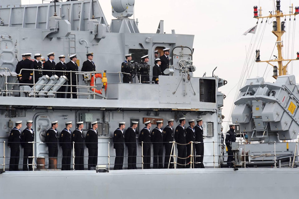 Members of HMS Chatham's crew lining her decks on the ship's final approach into Devonport Naval Base