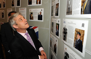 The Speaker of the House of Commons, John Bercow, views a display of 'Then & Now' images of armed forces veterans who now work within the parliament community