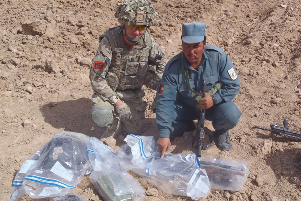 Training a member of the Afghan Uniform Police in how to gather and record evidence