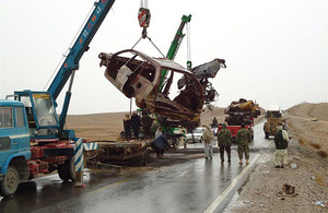 Afghan contractor clears the rusting hulks of abandoned vehicles from Highway 1, east of Lashkar Gah, Helmand province