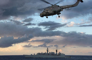 HMS Cumberland with the ship's Lynx helicopter flying overhead