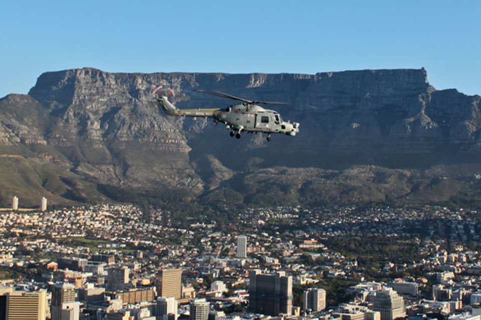 HMS Edinburgh's Lynx flies past Table Mountain in Cape Town