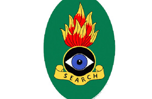 The oval-shaped badge is emblazoned with the word 'SEARCH', with a design of an eye and flame above it, to represent the nature of the Search Teams' work