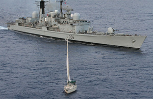 HMS Gloucester alongside the yacht Tortuga in the Atlantic Ocean