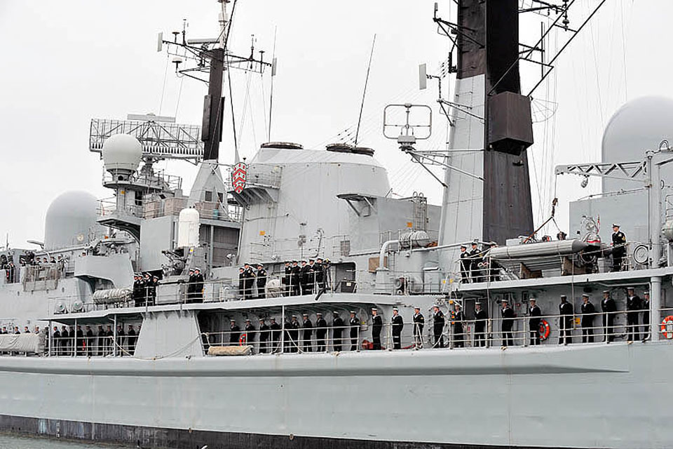 HMS Gloucester's ship's company line the decks as they leave Portsmouth for seven months