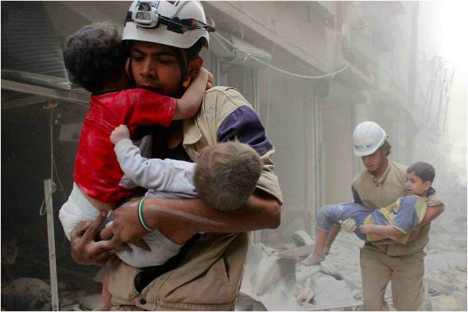 White Helmet worker carrying a child in Syria