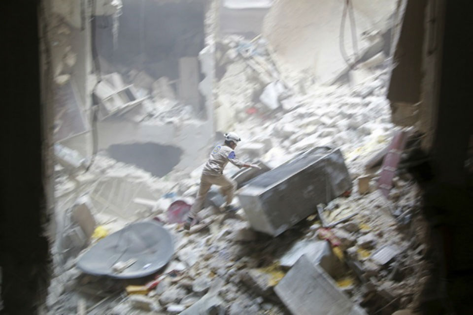 White Helmet worker surrounded by a collapsed building