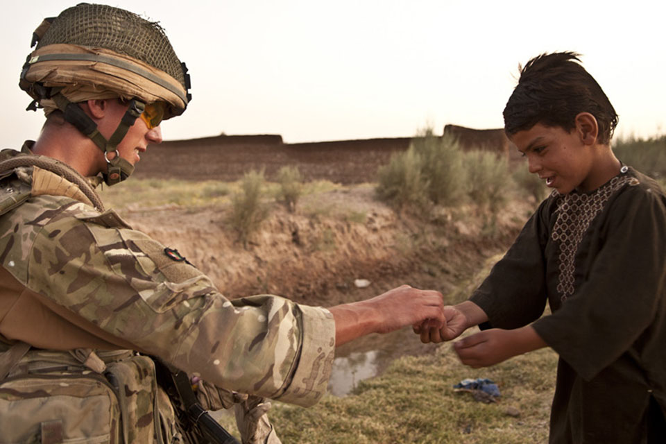 Highlander Mark Mackenzie, 4 SCOTS, gives an Afghan child a treat during a patrol in Lashkar Gah District, Helmand province