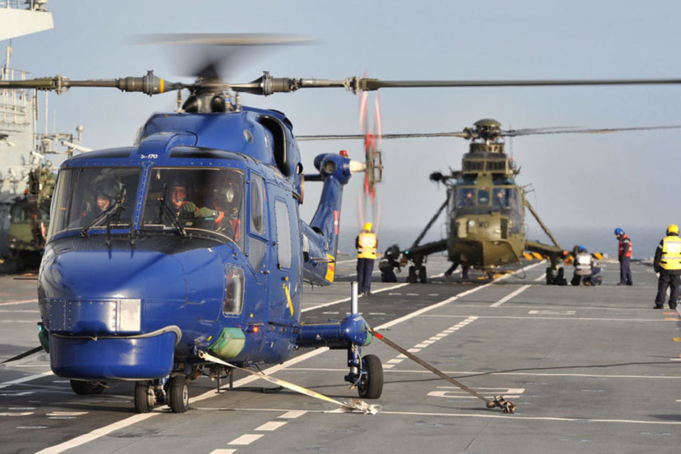 A Lynx helicopter from the Royal Danish Air Force (foreground) on board HMS Illustrious for flight deck drills