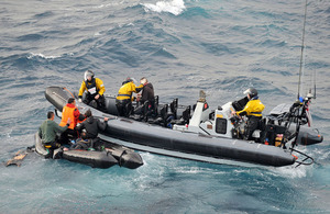 HMS Cornwall's sea boat recovers five people from a damaged four-metre inflatable boat