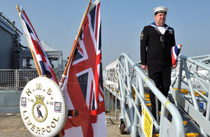 Able Seaman Anthony Clarke carries HMS Liverpool's folded White Ensign under his arm on the gangway