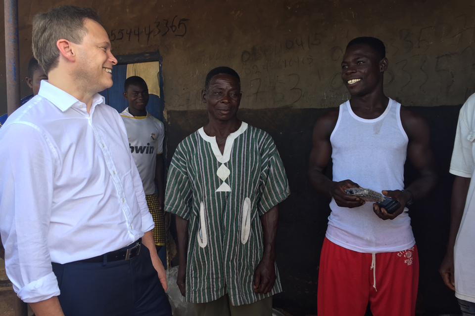 Minister Shapps talks to David and Gideon who have just had a PEG Ghana solar panel installed on their roof. Picture: Jessica Seldon/DFID.