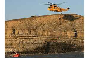 An RAF Sea King Search and Rescue helicopter lowers winchman Sergeant Rachel Robinson down the rock face at Dunraven Bay to reach the stranded teenagers