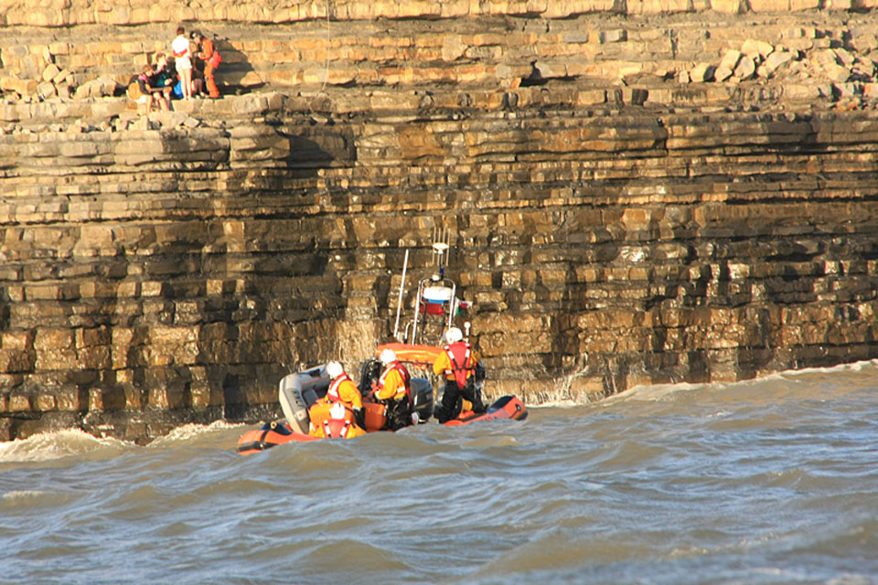 Sergeant Rachel Robinson prepares to lift the teenagers to safety as a lifeboat crew looks on from the sea below