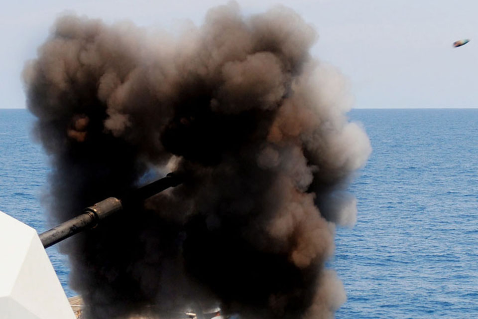 A 4.5-inch gun is fired from a Royal Navy warship, with the shell captured in flight