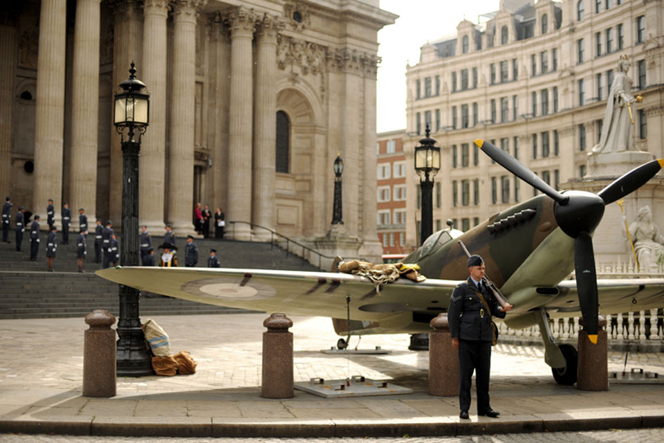 A re-enactor dressed as a wartime airman guards a replica Spitfire outside St Paul's Cathedral in London as a special service is conducted to commemorate the 70th anniversary of the Battle of Britain
