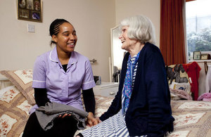 A social worker assisting an older lady.