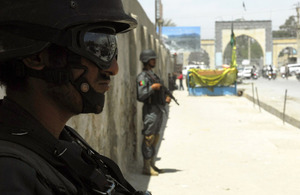 Afghan National Police on sentry duty at a marketplace in Kandahar City during a dismounted patrol