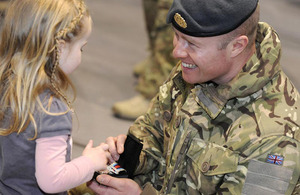 Corporal Jonathan Wilcox of 31 Squadron RAF, aged 32 from Kings Lynn, shows his daughter his Operational Service Medal