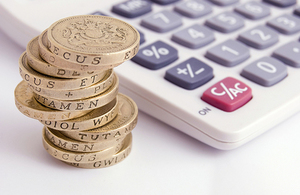 Pile of pound coins with calculator. Copyright iStock.