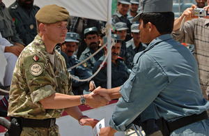 Soldier presents a graduation certificate to an Afghan policeman
