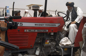 District Governor Habibullah Khan starts up the first tractor just outside Forward Operating Base Shawqat in the district centre of Nad 'Ali