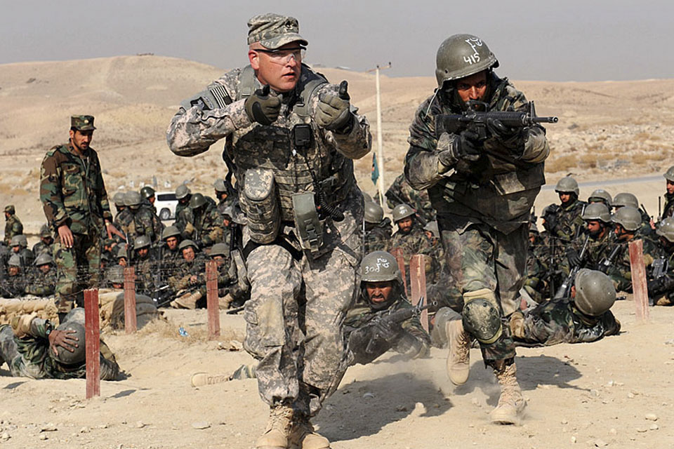 A United States Army mentor mirrors an Afghan National Army trainee for technique corrections during a field training exercise at the Kabul Military Training Centre