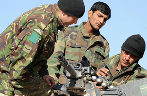 Lance Corporal Wiltshire shows Afghan warriors how to operate a grenade machine gun