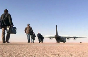 Oilfield workers make their way to an RAF C-130 Hercules