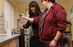 Two women talking in kitchen.