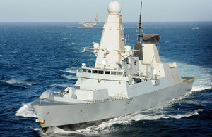 HMS Daring, with USS Carl Vinson in the background, en route to Qatar for the Doha International Maritime Defence Exhibition and Conference