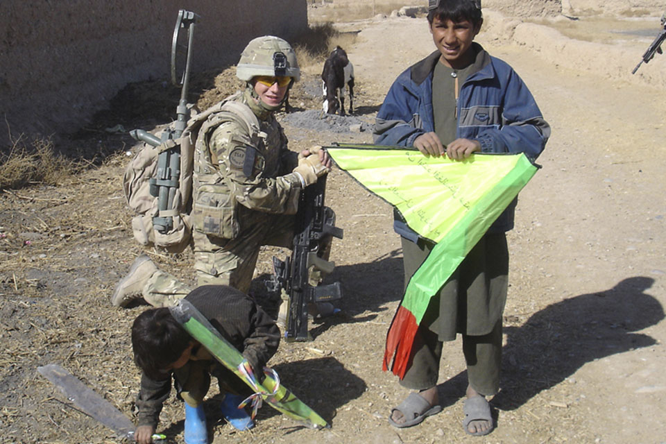 A soldier from 2nd Battalion The Royal Regiment of Scotland with local Afghan children and their new kites