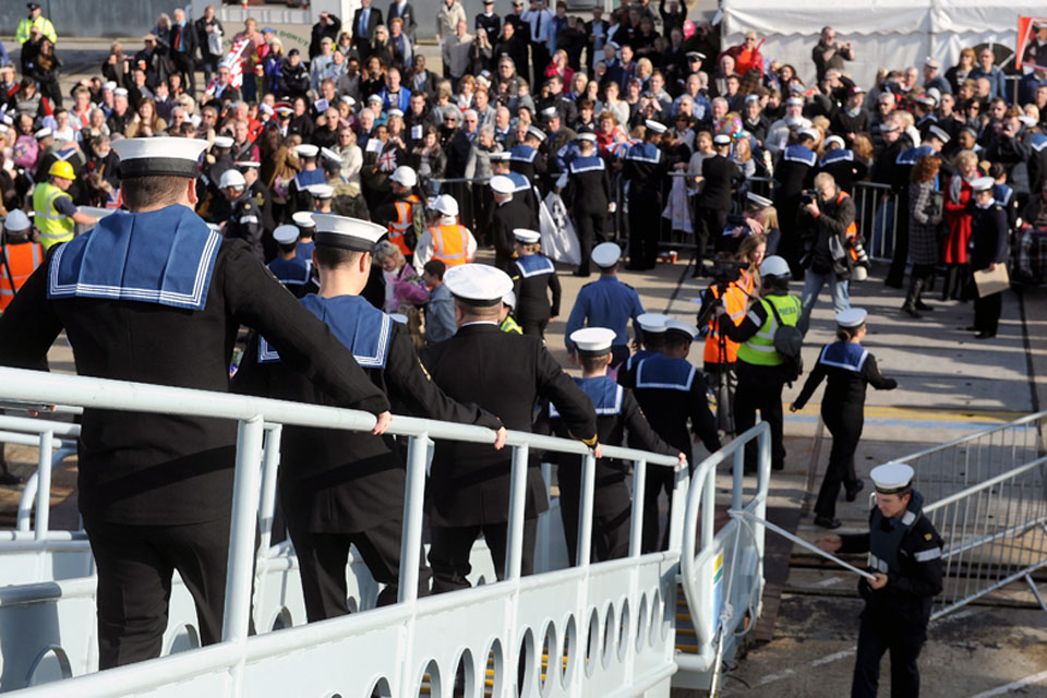 Sailors descend the gangway from HMS Dauntless onto dry land at Portsmouth