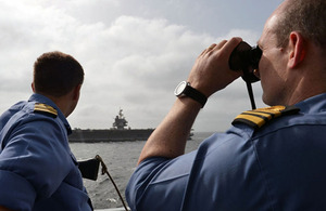 Members of HMS Diamond's ship's company observe flight deck operations being conducted on the USS Enterprise
