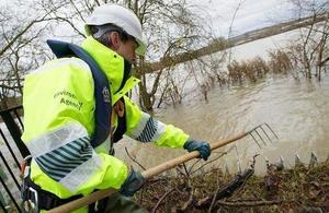 Environment Agency staff member clearing flood defences