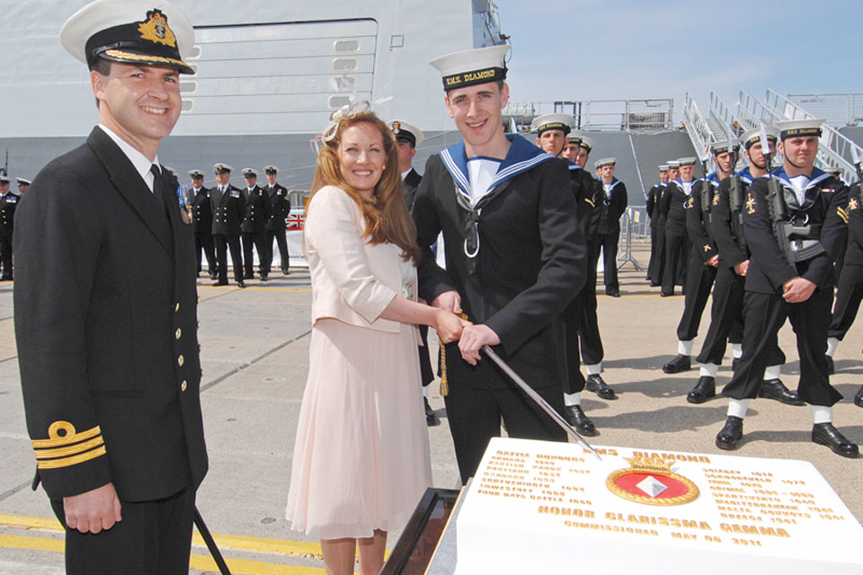 From left: Commanding Officer of HMS Diamond, Commander Ian Clarke, watches as his wife Joanne and the youngest member of the ship's company, Engineering Technician Ross Hindmarch, cut the commissioning cake