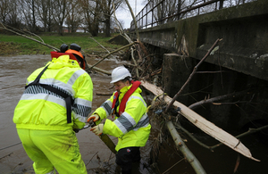 2 Environment Agency staff under a bridge clearing debris from a watercourse